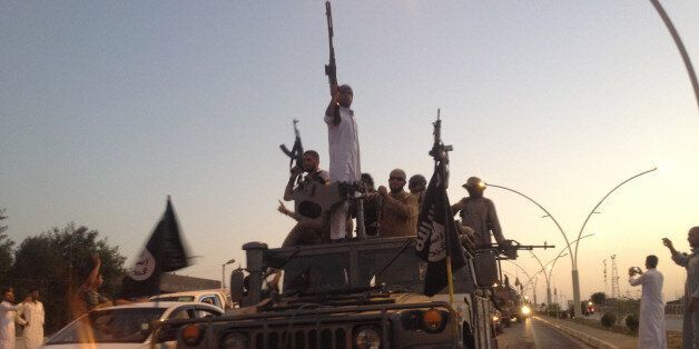 In this photo taken Monday, June 23, 2014, fighters of the al-Qaida-inspired Islamic State of Iraq and the Levant (ISIL) para