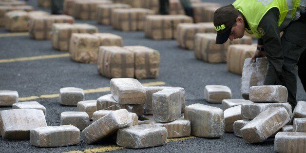 A Colombian anti-drugs police officer checks packages of marijuana, part of a load of five tons seized in the outskirts of Ca