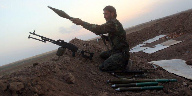 A Peshmerga fighter loads a weapon as he guards a position on front line of fighting with Islamic State (IS) militants 20 kil