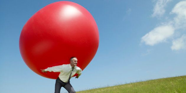 Businessman carrying large ball up a