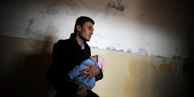 A man holds a baby as he waits to receive aid distributed by the Bulgarian Red Cross and the Medical University of Sofia in t