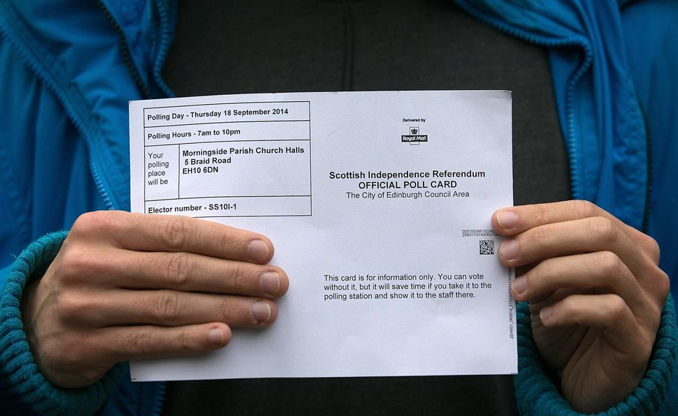 A voter holds up his polling card outside a polling place in Morningside, Edinburgh on Sept.18, 2014.
