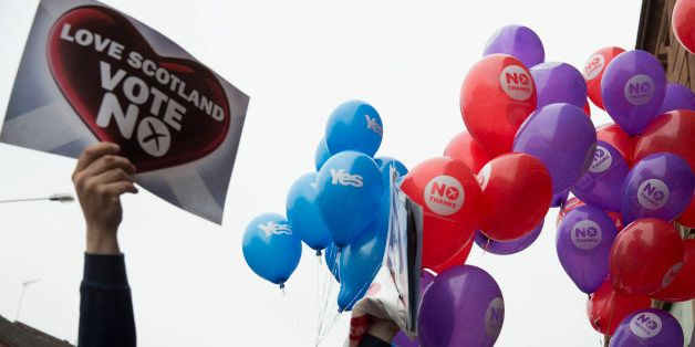 Balloons held by Yes supporters float next to balloons and posters held by No supporters after a No campaign event where a nu