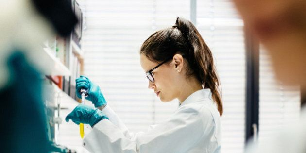 Female scientist using pipette in a modern laboratory, Her female colleague using microscope in