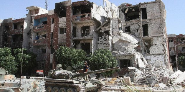 DAMASCUS, SYRIA - SEPTEMBER 25: Tanks of Assad forces are seen around the destroyed buildings during the clashes between Syri