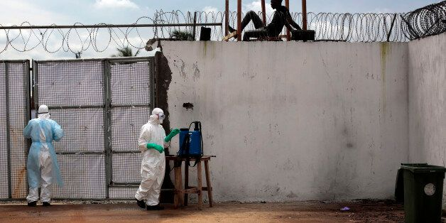 Health workers stand outside the Island Clinic Ebola isolation and treatment center in Monrovia, Liberia, Friday Sept. 26, 20