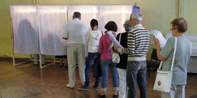 People wait on September 14, 2014 before voting at a polling station in Simferopol during combined regional and local electio
