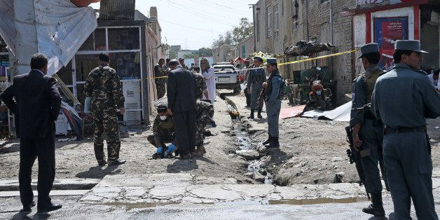 Afghan security forces inspect the site of a suicide attack near the International Airport of Kabul, Afghanistan, Monday, Sep