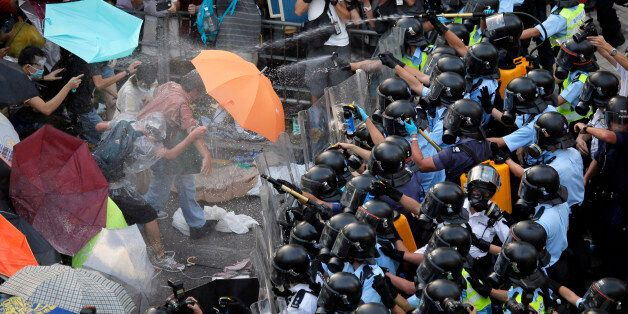 Riot police use pepper spray against protesters after thousands of people block a main road to the financial central district outside the government headquarters in Hong Kong, Sunday, Sept. 28, 2014. A tense standoff between thousands of Hong Kong pro-democracy protesters and police warning of a crackdown spiraled into an extraordinary scene of chaos Sunday as the crowd jammed a busy road and clashed with officers wielding pepper spray. (AP Photo/Vincent Yu)