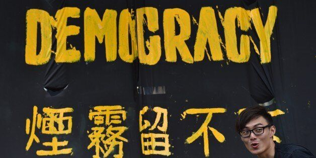 A pro-democracy protester stands next to a banner in Hong Kong on September 30, 2014. China on September 30 called major pro-democracy demonstrations in Hong Kong 'illegal', as state media insisted Beijing would not give in but would wait for public opinion to turn against the protests. AFP PHOTO / Philippe Lopez (Photo credit should read PHILIPPE LOPEZ/AFP/Getty Images)