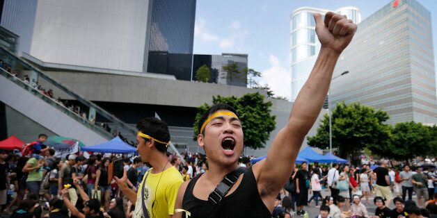 A pro-democracy activist shouts slogans on a street near the government headquarters where protesters have made camp, Wednesd