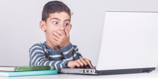 Young boy reacts while using a laptop. Internet safety for kids concept. Toned image with selective
