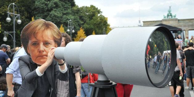 BERLIN, GERMANY - AUGUST 30: A woman holding a mock telescope and wearing a mask showing German Chancellor Merkel attends the