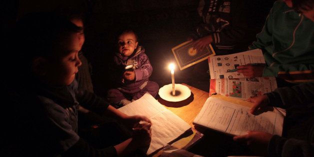 GAZA CITY, GAZA - MARCH 15:  Palestinian children sit inside thier makeshift house during power cuts in Khan Younis in the so