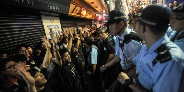 HONG KONG - OCTOBER 04: Pro-democracy protestors raise their hands as Hong Kong police officers take security measures in the