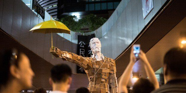 The statue 'Umbrella Man' by the Hong Kong artist known as Milk, is set up at a pro-democracy protest site next to the central government offices in Hong Kong on October 5, 2014. Pro-democracy demonstrators stood divided Sunday over whether to withdraw from protest sites across Hong Kong, hours before a government deadline to clear key roads they have blockaded for the last week. Embattled Chief Executive Leung Chun-ying has said his administration was determined to 'take all necessary actions to restore social order' and pave the way for government staff to resume work by Monday morning. AFP PHOTO / ALEX OGLE RESTRICTED TO EDITORIAL USE, MANDATORY CREDIT OF THE ARTIST, TO ILLUSTRATE THE EVENT AS SPECIFIED IN THE CAPTION (Photo credit should read Alex Ogle/AFP/Getty Images)