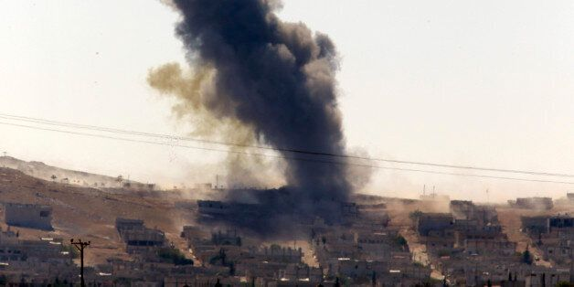 Smoke rises after a shell lands in Kobani in Syria as fighting intensifies between Syrian Kurds and the militants of Islamic
