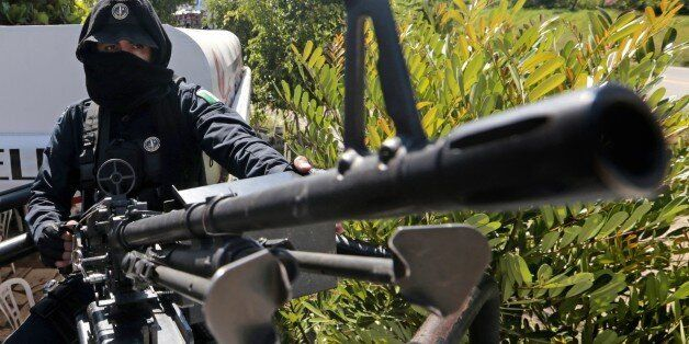A federal police officer mans a general-purpose machine gun (GPMG) at a checkpoint in Iguala, Guerrero State, Mexico, on Octo
