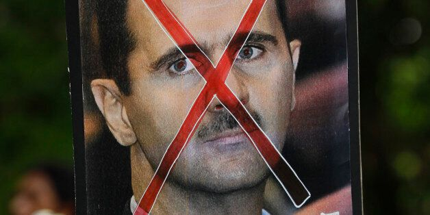 A protester holds up a poster of Syrian President Bashar al-Assad with cross mark over it during a protest rally against Assa
