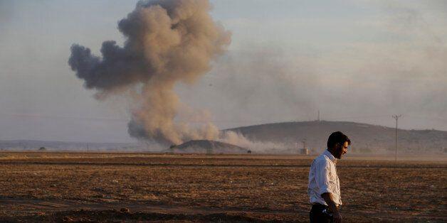 A Turkish Kurd walks away as airstrikes hit Kobani, inside Syria, as fighting intensifies between Syrian Kurds and the milita