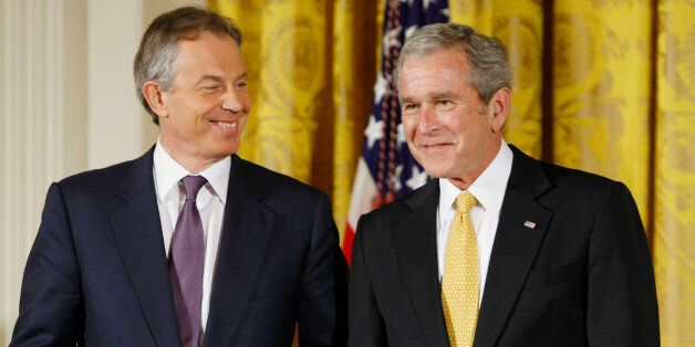 President George W. Bush and former British Prime Minister Tony Blair nudge each other in the East Room of the White House in