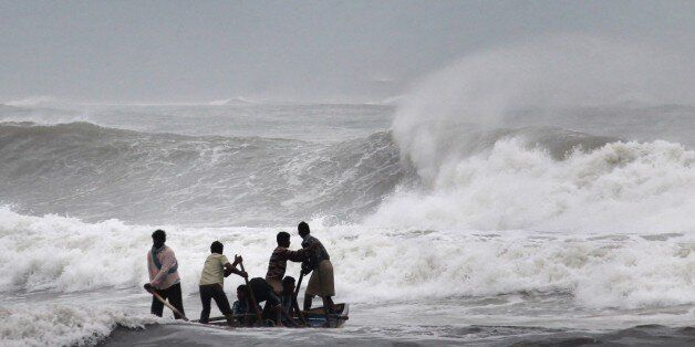 Indian fishermen negotiate their skiff through rough waves ahead of Cyclone Hudhud making expected landfall in Visakhapatnam