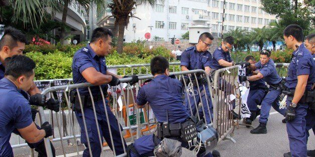Police officers remove barricades from pro-democracy demonstrators (unseen) near the government offices in Hong Kong on October 13, 2014. Dozens of Hong Kong police were massing at protest sites where pro-democracy demonstrators have been holding more than two weeks of rallies, paralysing parts of the Asian financial hub. AFP PHOTO / Laurent FIEVET (Photo credit should read LAURENT FIEVET/AFP/Getty Images)