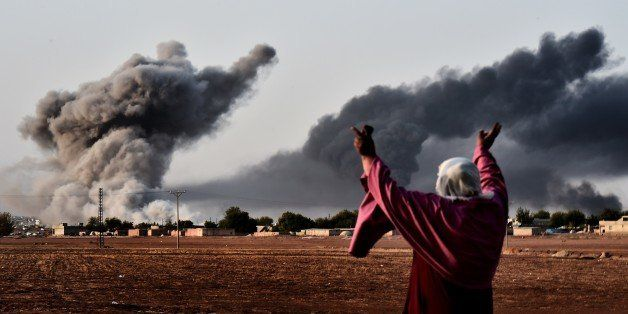 A woman reacts as smoke rises from the the Syrian town of Ain al-Arab, known as Kobane by the Kurds, after a strike from the
