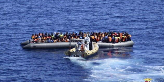 Migrants sit in their boat during a rescue operation by Italian Navy vessels off the coast of Sicily...