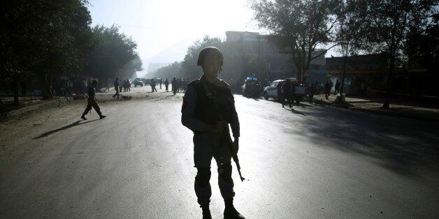 An Afghan security soldier stands guard at the site of a suicide attack in Kabul, Afghanistan, Wednesday, Oct. 1, 2014. Two s