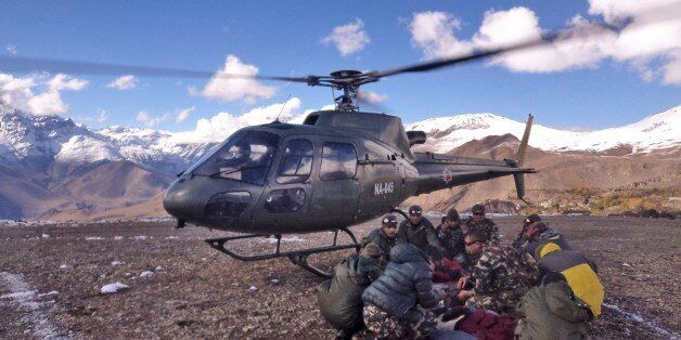 In this photo provided by the Nepalese army, soldiers prepare to airlift an avalanche victim in Thorong La pass area, Nepal,