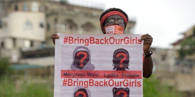 A supporter of the #BringBackOurGirls campaign carries a placard showing the missing faces of the kidnapped Chibok schoolgirl