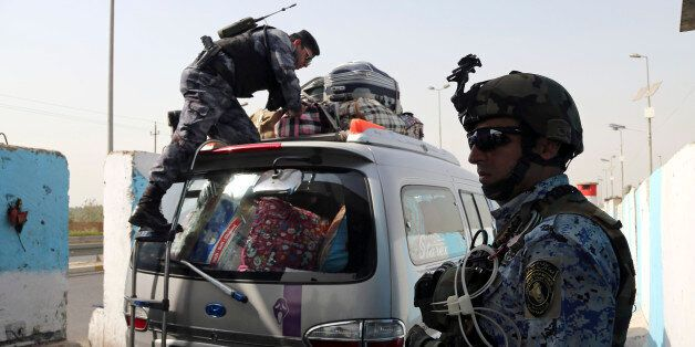 An Iraqi federal policeman stands guard as his colleague searches a car at a checkpoint in Baghdad, Iraq, Saturday, Oct. 11,