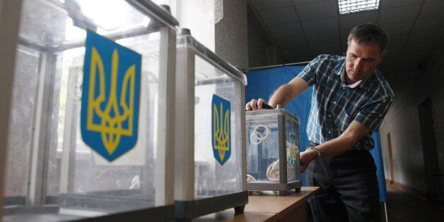 A member of the election commission prepares ballot boxes at one of the polling stations in Kiev on May 24, 2014, a day befor