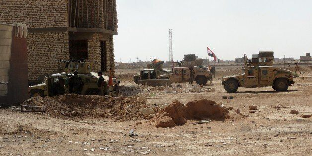 Iraqi security forces and gunmen take positions following clashes with jihadists on September 19, 2014, in Ramadi, the capita