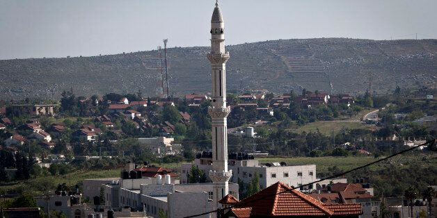 In this April 17, 2014 photo, the minaret of the main mosque of the Palestinian village of Silwad overlooks the adjacent Israeli settlement of Ofra, in the background, north of the West Bank city of Ramallah. (AP Photo/Nasser Nasser)