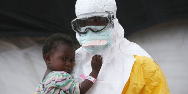 PAYNESVILLE, LIBERIA - OCTOBER 05:  A Doctors Without Borders (MSF), health worker in protective clothing holds a child suspe