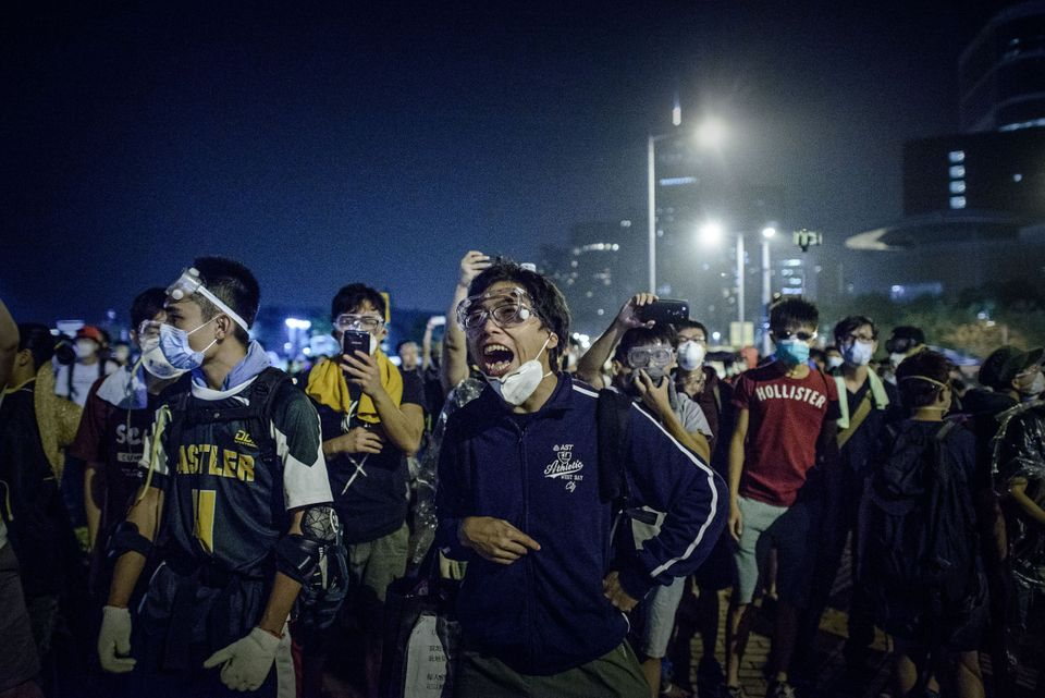 Pro-democracy protesters shout at police forces outside the central government offices in Hong Kong on October 14, 2014. Hong