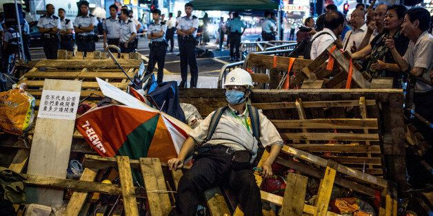 HONG KONG - OCTOBER 24:  A pro-democracy protester guards a barricade  from pro-China supporters on a street in Mong Kok on O