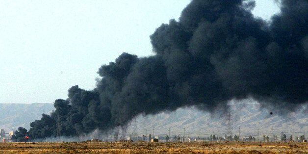 The thick black smoke from an oil pipeline fire in Baji 38 kilometers, 23 miles from Tikrit, Iraq, Thursday, Sept. 18, 2003,