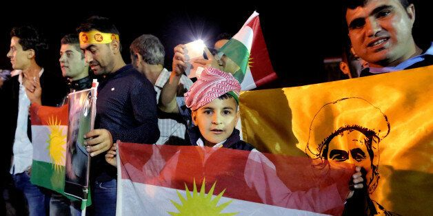 In this Tuesday, Oct. 28, 2014 photo, supporters of Kurdish Peshmerga forces hold a Kurdish flags as they wait for the troops