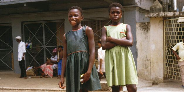 Two young girls pose for the camera along Fourah Bay Road in Freetown, Sierra Leone, March 1985 (Photo by Frances M. Ginter/G