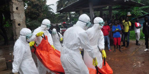 Health workers carry the body of a man suspected to have died of Ebola virus in Paynesville Community situated on the outskir