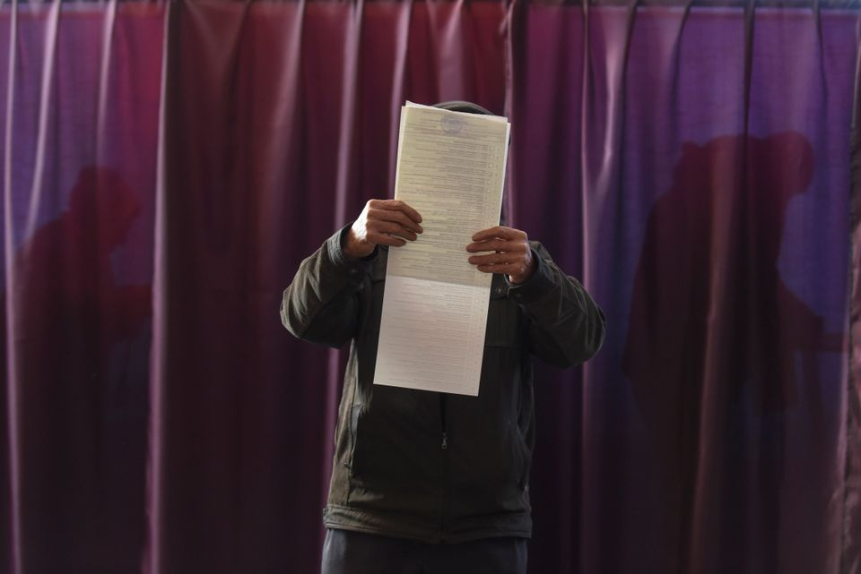 A man reads a ballot paper before casting his vote for the parliamentary elections at a polling station in Konstantinovka, Do