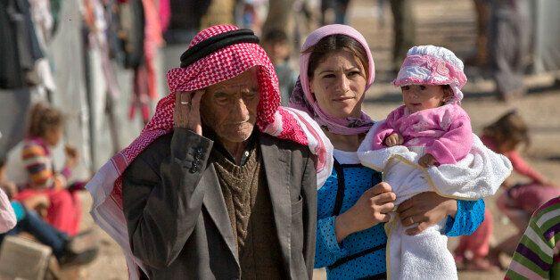 Syrian Kurdish refugees from the Kobani area walk at a camp in Suruc, near the Turkey-Syria border Monday, Nov. 3, 2014. Koba