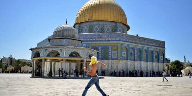 A Palestinian youth hurls stones at Israeli police officers, not seen, next to the Dome of the Rock Mosque in the Al Aqsa Mos