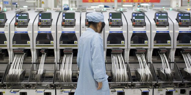 An employee monitors machinery used to adhere components to smartphone circuit boards in a manufacturing facility at ZTE Corp