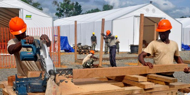 In this photo taken on Friday, Oct. 24, 2014, Liberian troops work to build a new section of an Ebola treatment center in the
