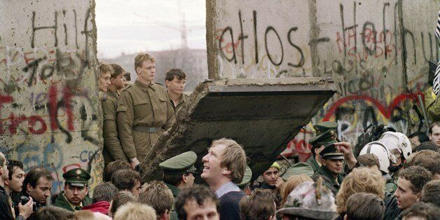 West Berliners crowd in front of the Berlin Wall early 11 November 1989 as they watch East German border guards demolishing a