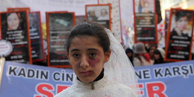 A Turkish girl, wearing a wedding dress and covered with fake bruises, stands in front of other protesters...
